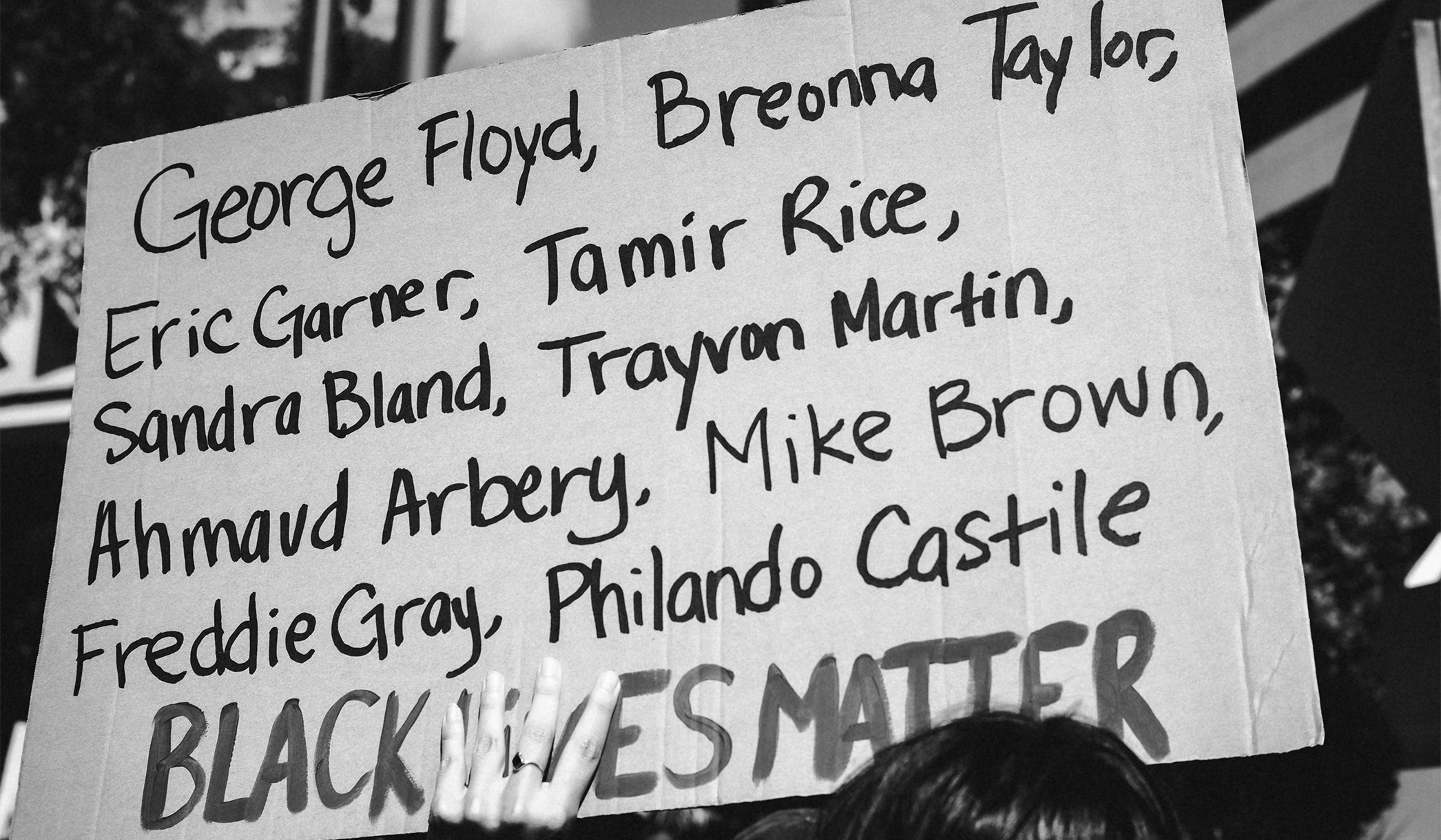 A protest sign featuring the names George Floyd, Breonna Taylor, Eric Garner, Tamir Rice, Sandra Bland, Trayvon Martin, Ahmaud Arbery, Mike Brown, Freddie Gray, and Philando Castile above the words Black Lives Matter.
